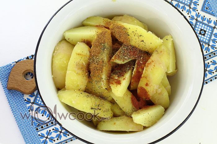 Перемещаем картофель в емкость для запекания и добавляем приправу