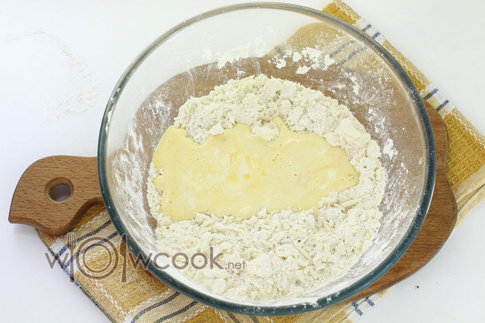 Отдельно перемешиваем желтки со сметаной и добавляем к сухой смеси