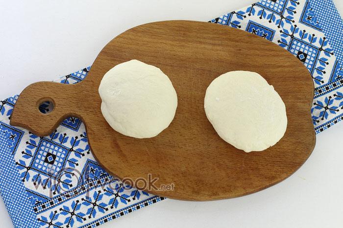 Обминаем тесто на подпыленной доске и разделяем на два кусочка